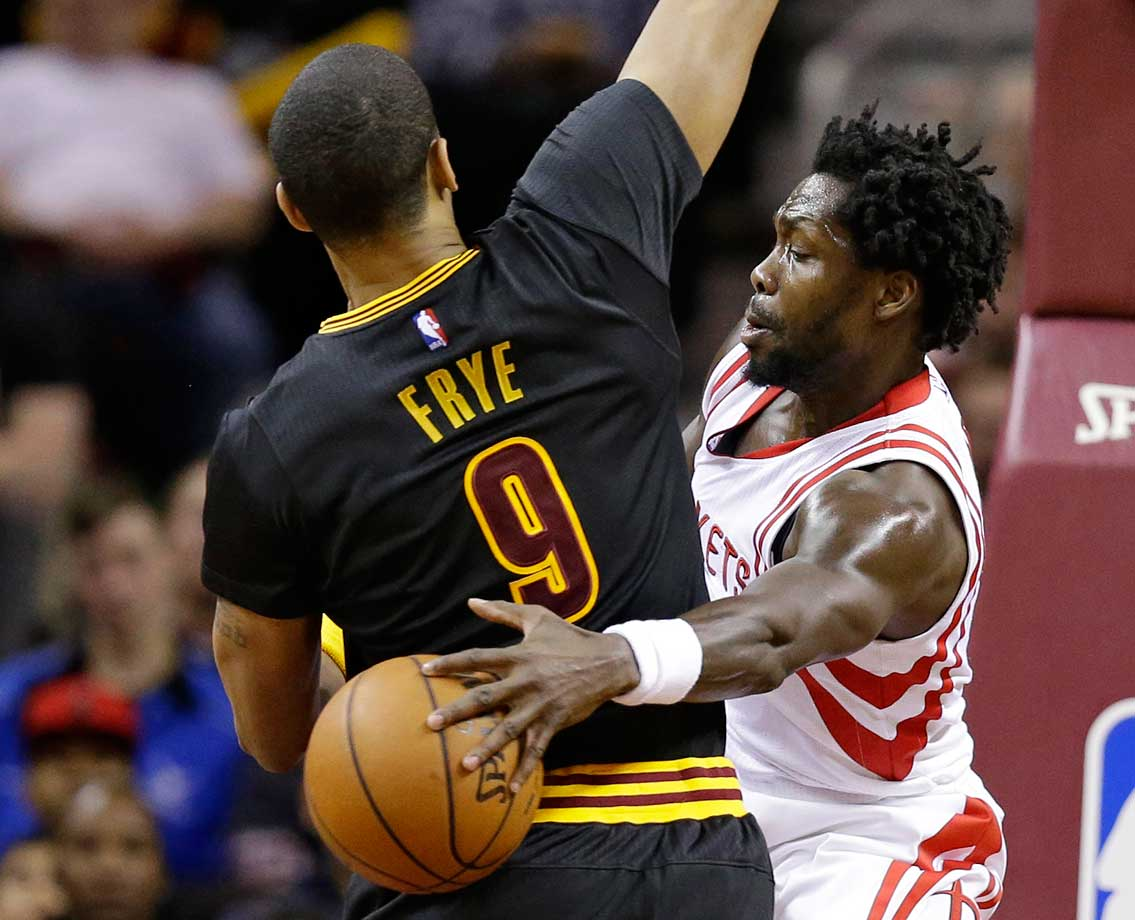Patrick Beverley of the Houston Rockets passes around Channing Frye of Cleveland.