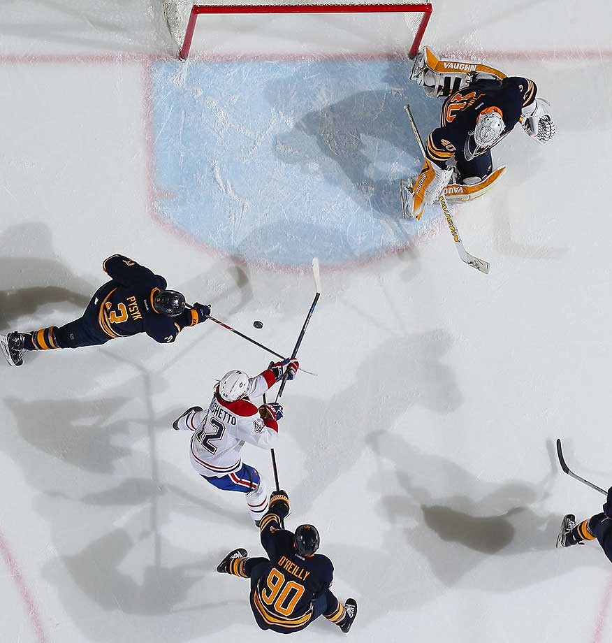 Robin Lehner of Buffalo makes a save as Ryan O'Reilly (90) and Mark Pysyk defend against Sven Andrighetto of Montreal.