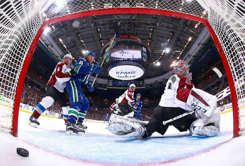 Alexandre Grenier of Vancouver and Erik Johnson of Colorado watches as Henrik Sedin scores on Semyon Varlamov.