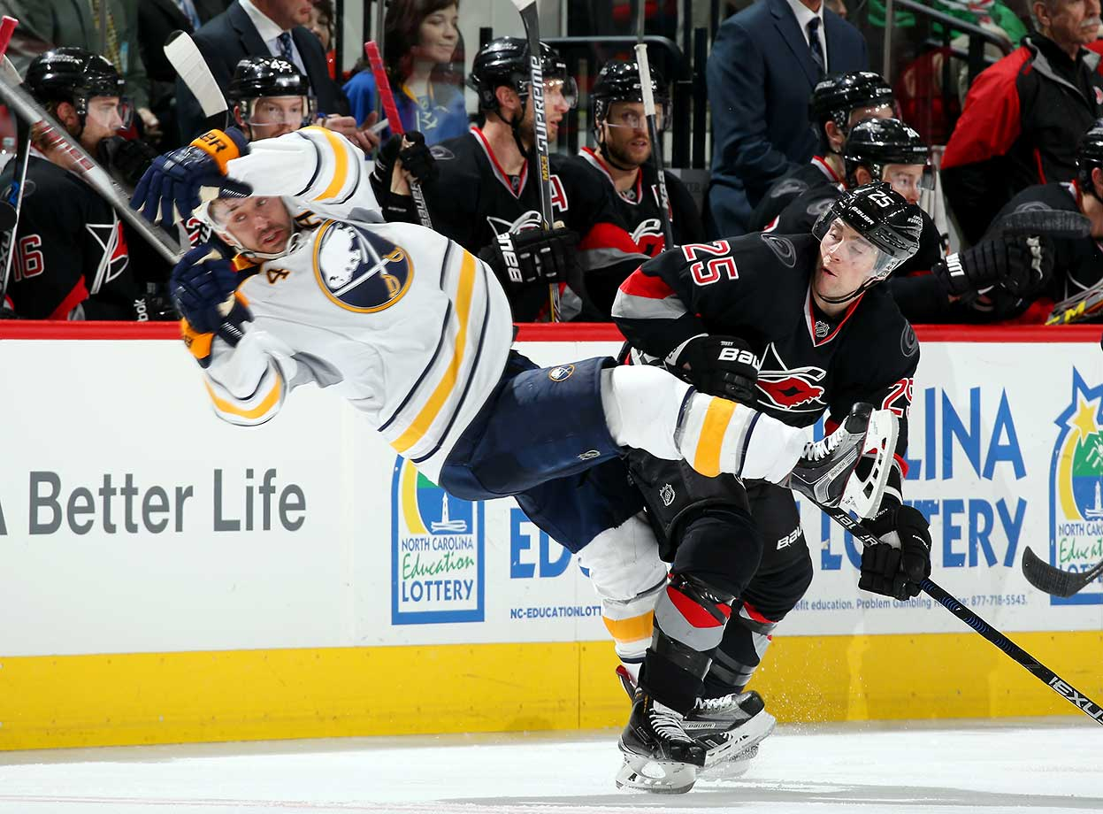 Chris Terry of the Carolina Hurricanes lands a heavy hit on Josh Gorges of the Buffalo Sabres.