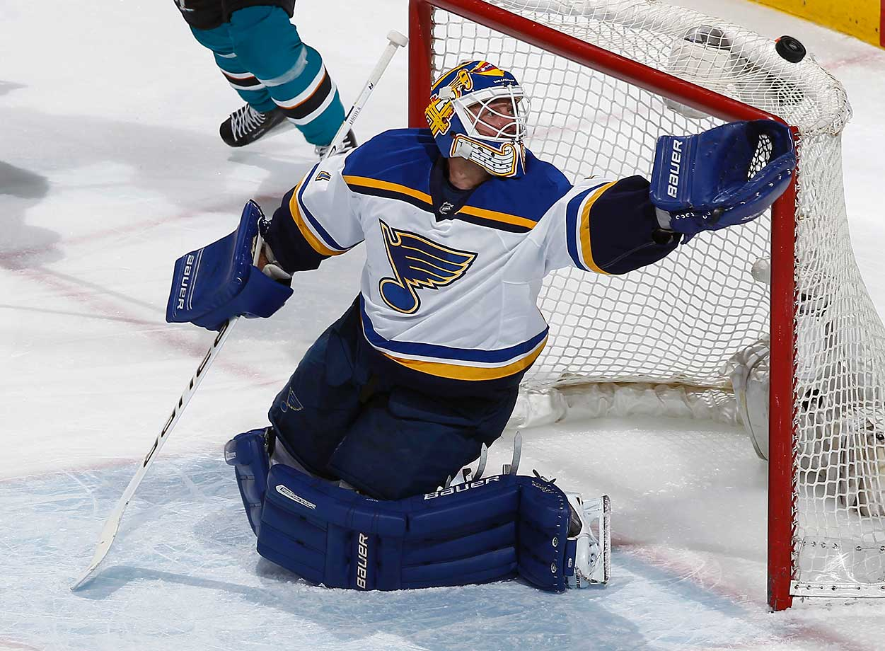 Brian Elliott of the St. Louis Blues makes a glove save against the San Jose Sharks.