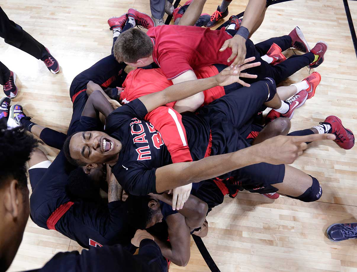 Mid-America Christian's Nick Tate (25) and his teammates celebrate their buzzer-beating 100-99 overtime win against Georgetown (Ky.) in the NAIA basketball championship game.