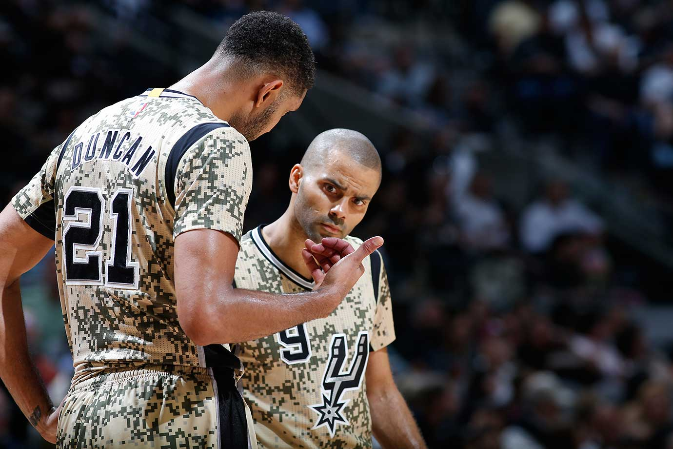 Tim Duncan and Tony Parker conversing in their camouflage uniforms during a game against the Miami Heat.