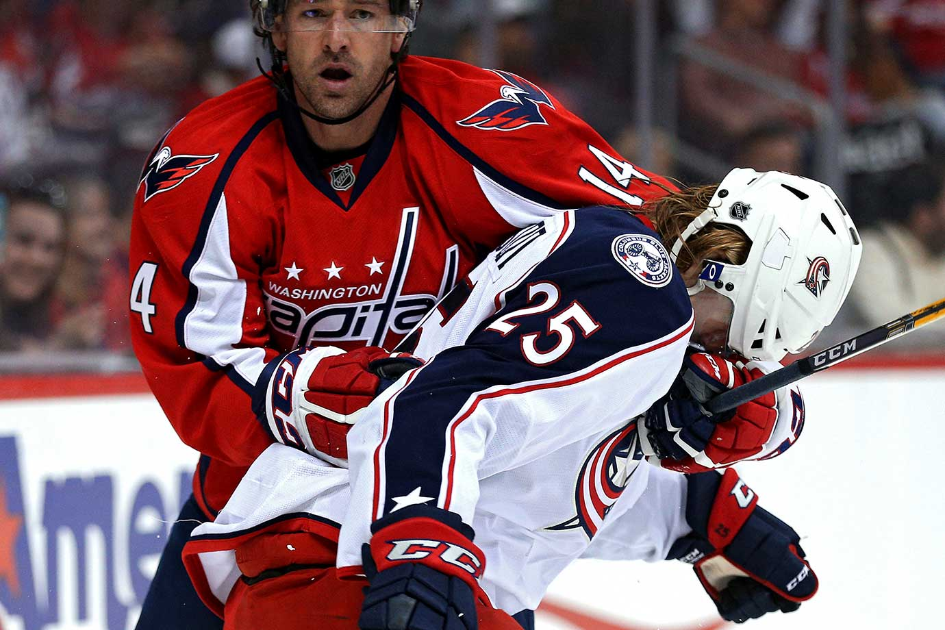 Justin Williams of the Washington Capitals rearranges the head gear of William Karlsson of the Columbus Blue Jackets.
