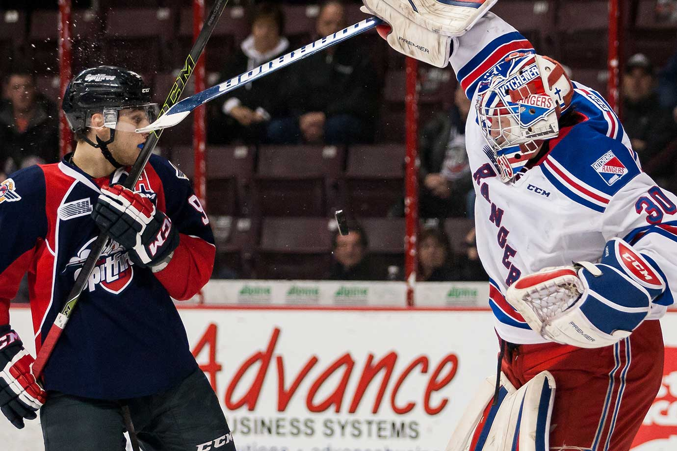 Goaltender Dawson Carty of the Kitchener Rangers battles for the puck (middle of picture) against Cristiano DiGiacinto of the Windsor Spitfires during Game 3 of the Western Conference quarterfinal series in the Ontario Hockey League.