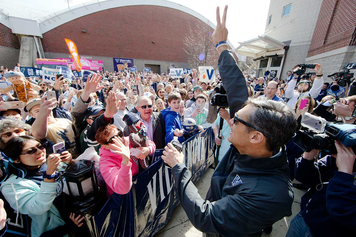 Villanova head coach Jay Wright gestures to fans as the team departs for the Final Four in Houston.