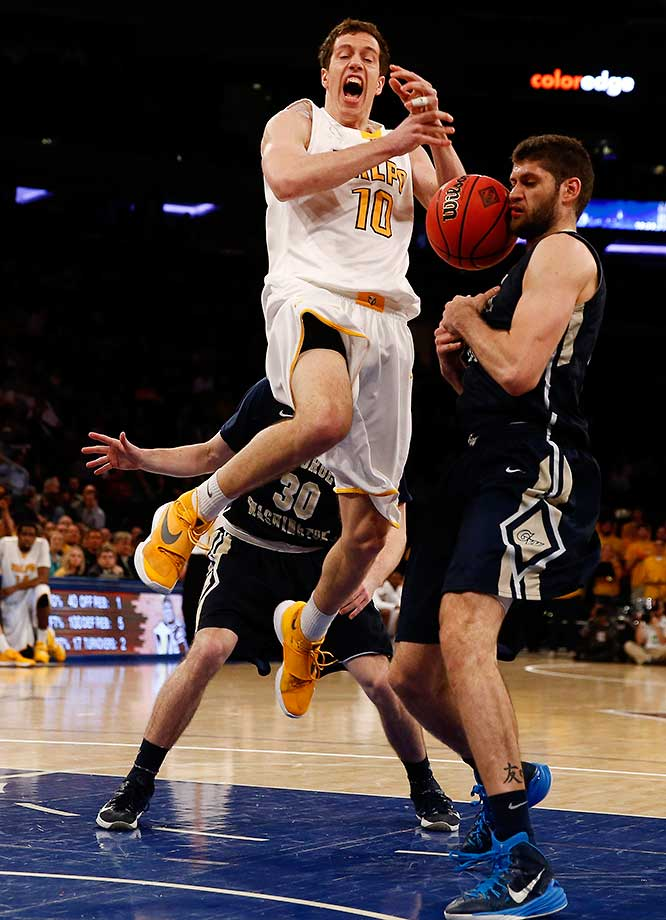 David Skara of Valparaiso is defended by Patricio Garino of George Washington during their NIT Championship game.