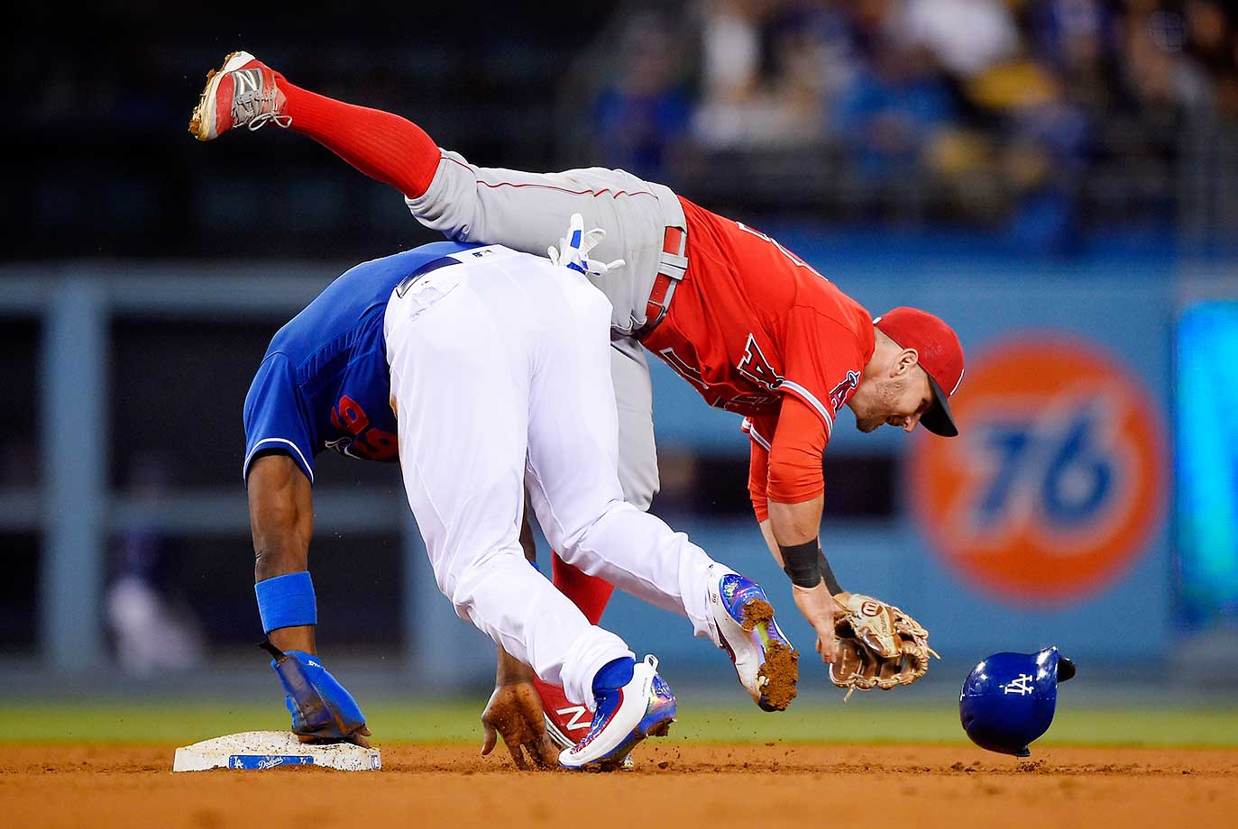 Angels second baseman Johnny Giavotella is upended by Yasiel Puig of the Dodgers as Puig steals second and heads to third on a throwing error by catcher Carlos Perez.