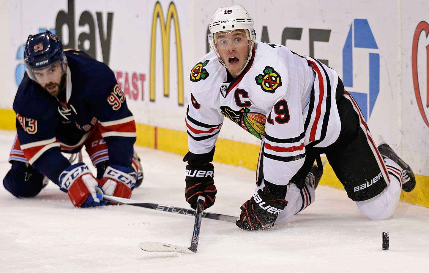 Chicago center Jonathan Toews (19) falls to the ice battling for the puck with New York defenseman Keith Yandle.
