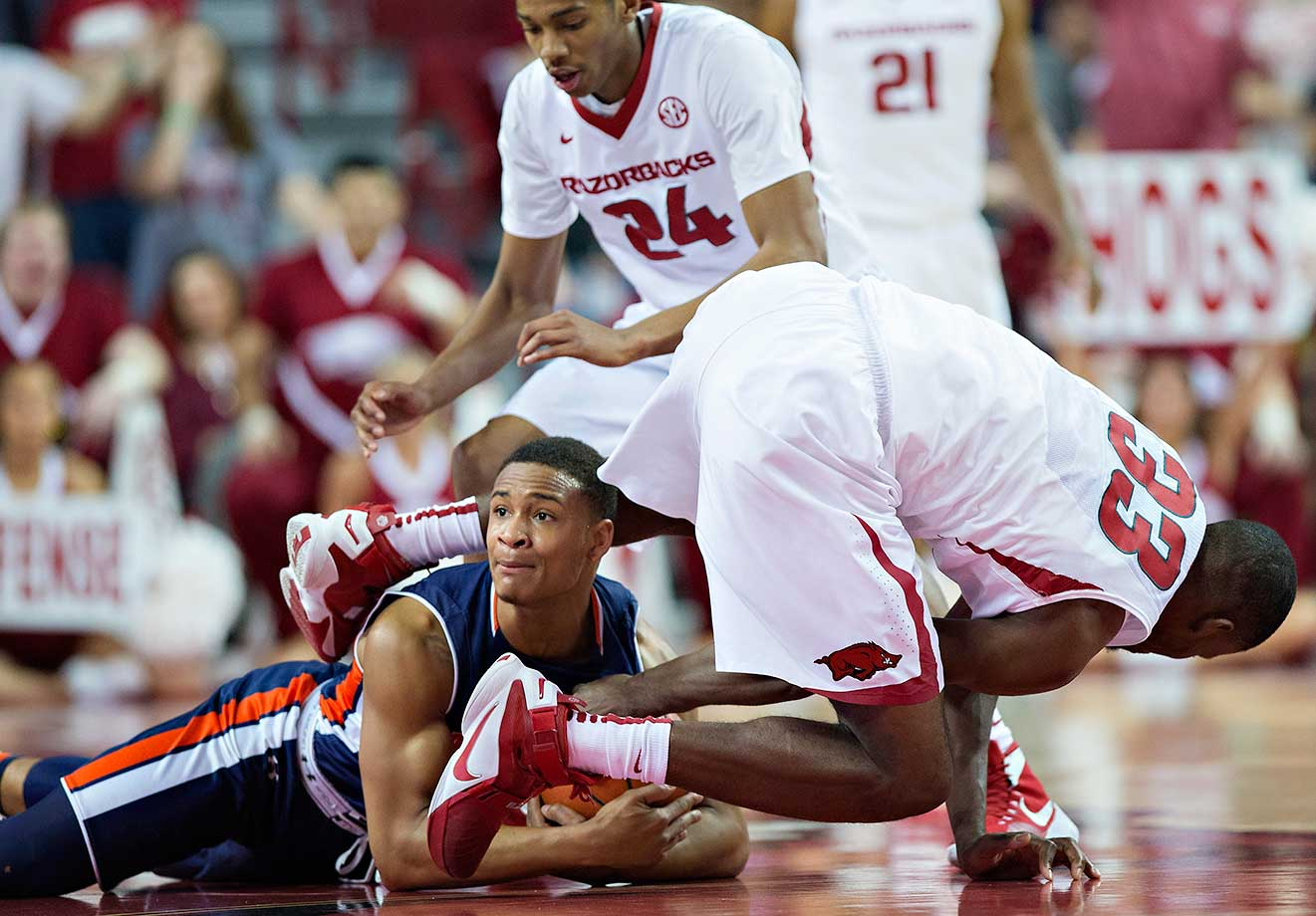 Bryce Brown of Auburn dives to the floor for a loose ball against Moses Kingsley of Arkansas.