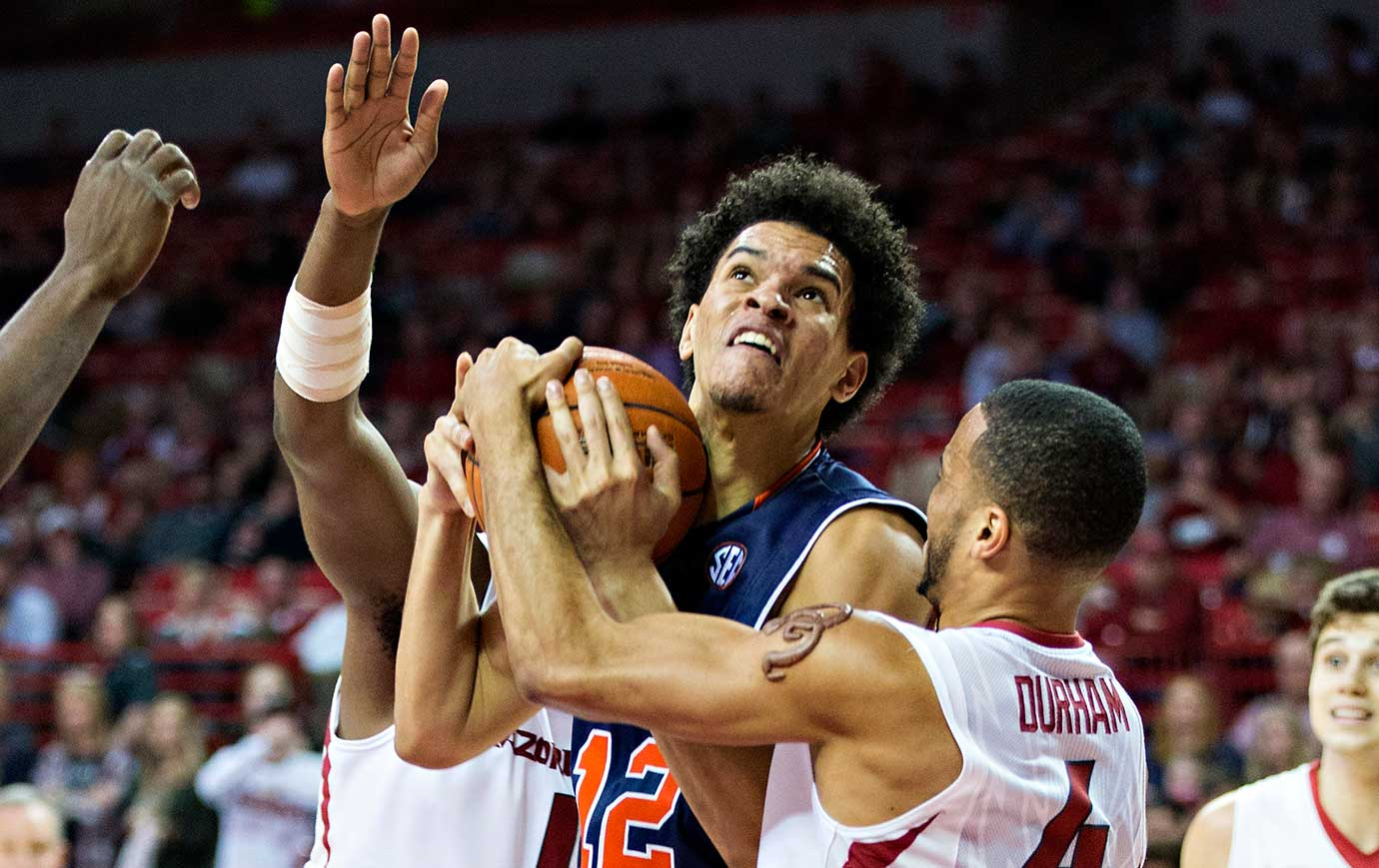 Tyler Harris of the Auburn Tigers is tied up and fouled by Jabril Durham of the Arkansas Razorbacks.
