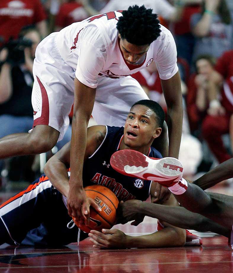 Auburn's Bryce Brown keeps the ball underneath him as Arkansas' Jimmy Whitt tumbles over.