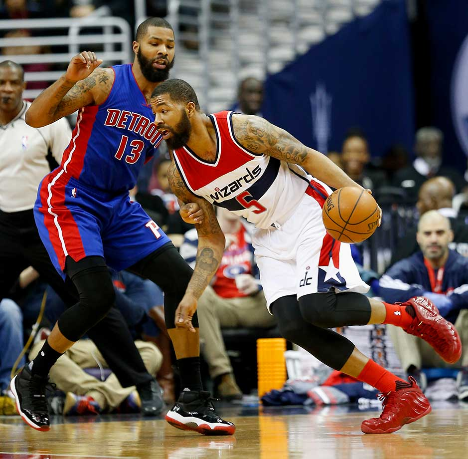Markieff Morris of the Washington Wizards drives to the basket against his twin brother Marcus of the Detroit Pistons.