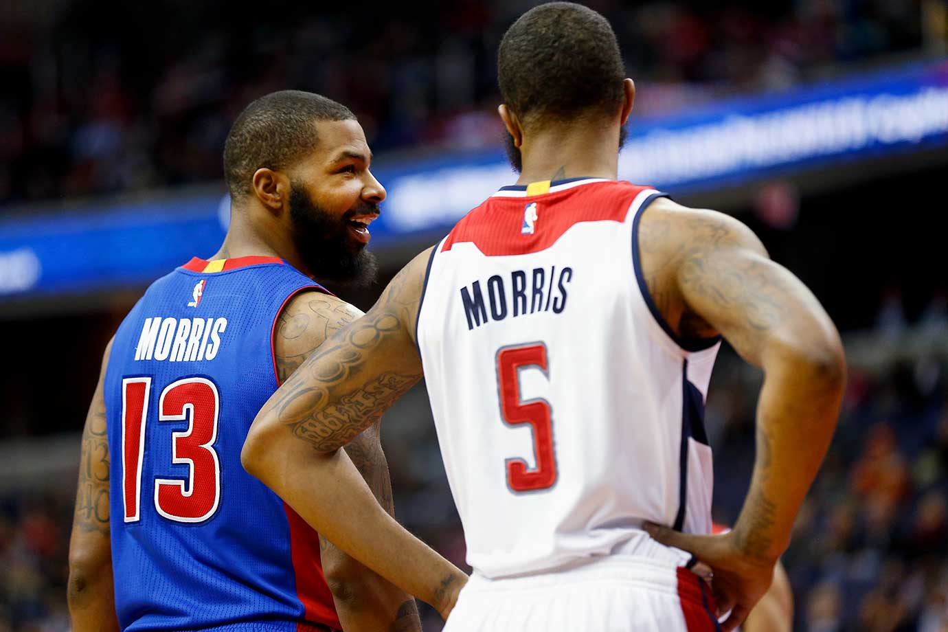 Marcus Morris of the Detroit Pistons talks with his twin brother Markieff of the Washington Wizards.
