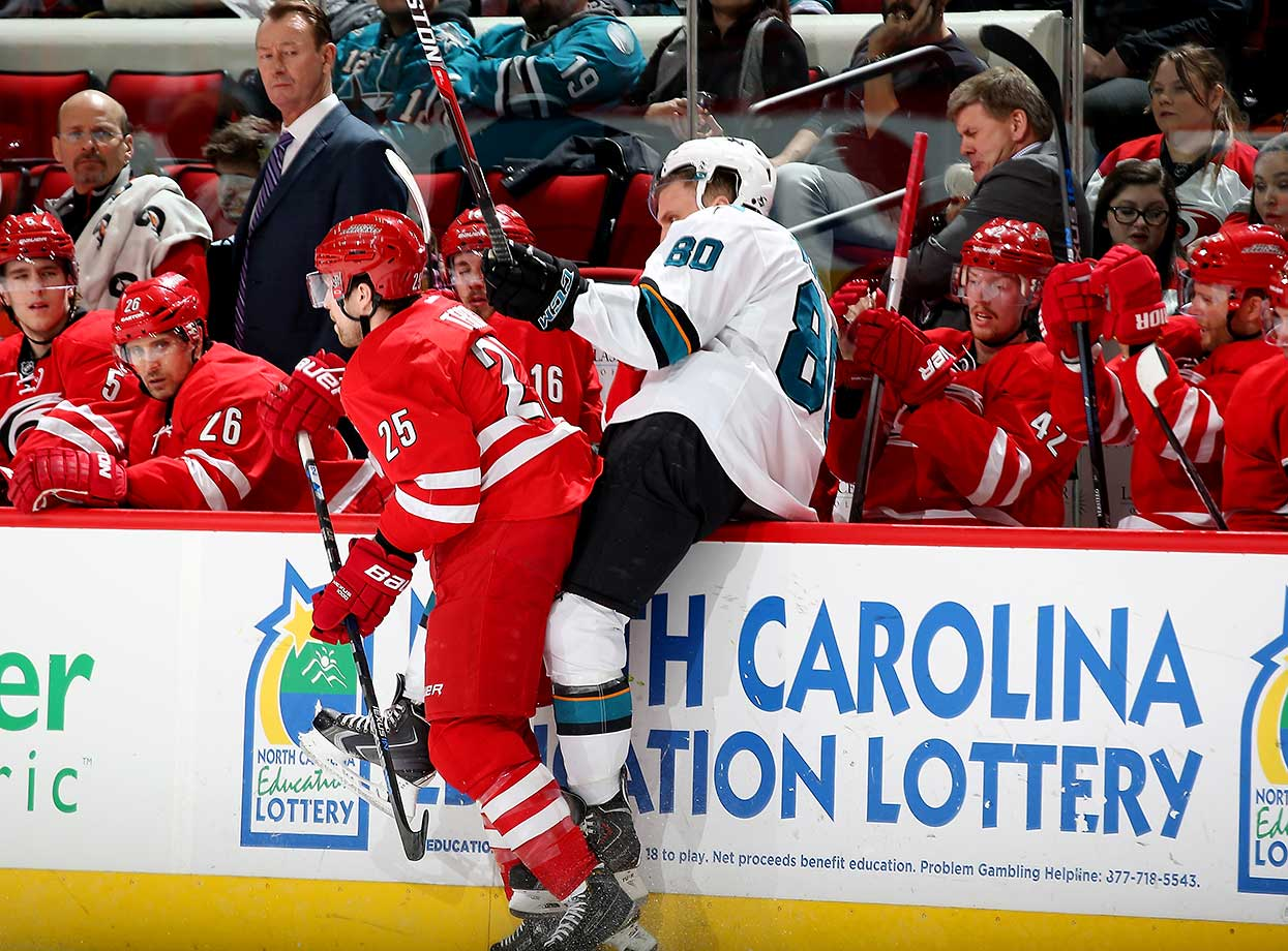 Chris Terry of the Carolina Hurricanes and Matt Tennyson of the San Jose Sharks get tangled up at the Hurricanes bench.
