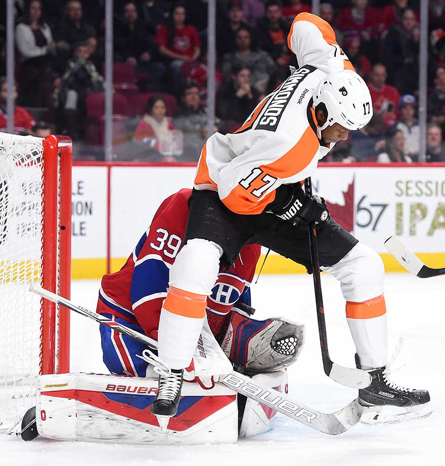 Wayne Simmonds of the Philadelphia Flyers attempts to deflect the puck against Mike Condon of the Montreal Canadiens.