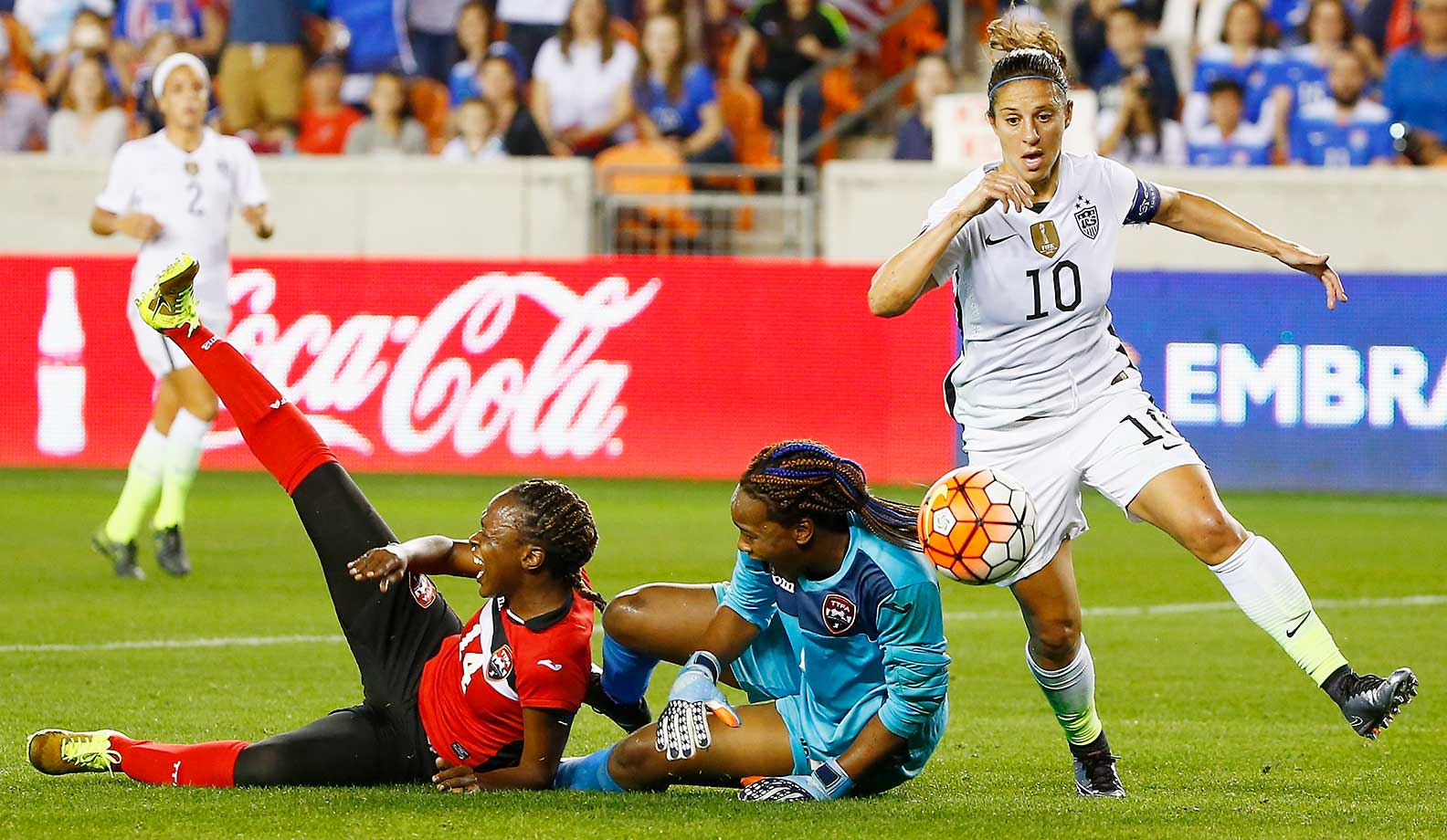 Carli Lloyd of the United States battles for the ball with keeper Kimika Forbes of Trinidad and Tobago.