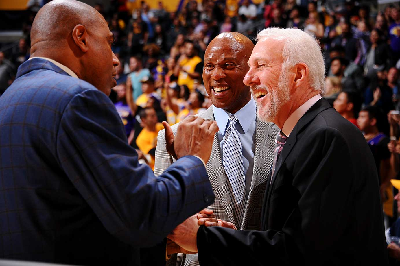 Head coach Byron Scott of the Lakers and Gregg Popovich of the San Antonio Spurs talk Magic Johnson before a game in L.A.