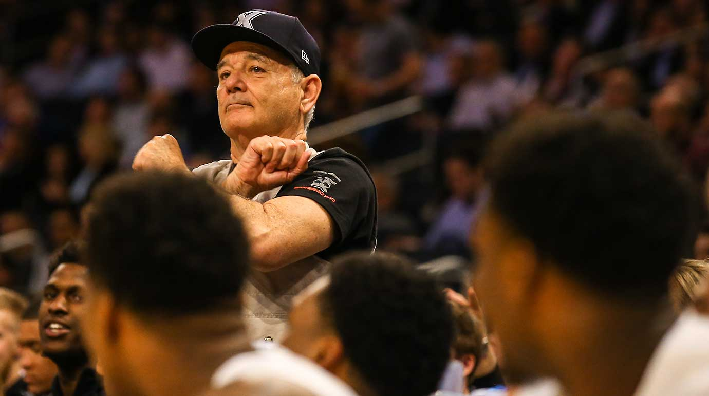 Actor Bill Murray crosses his arms and makes an X while Xavier Musketeers players turn and watch.
