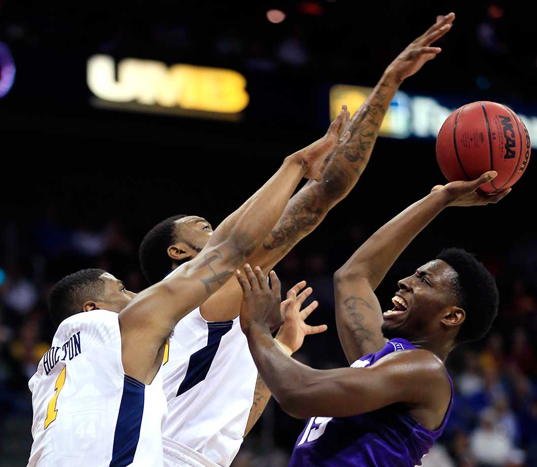 TCU forward JD Miller shoots over West Virginia's Jonathan Holton and Elijah Macon.