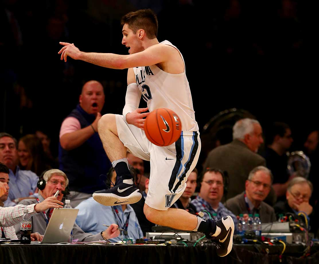 Ryan Arcidiacono of Villanova leaps into the front row to keep the ball in play against Georgetown.
