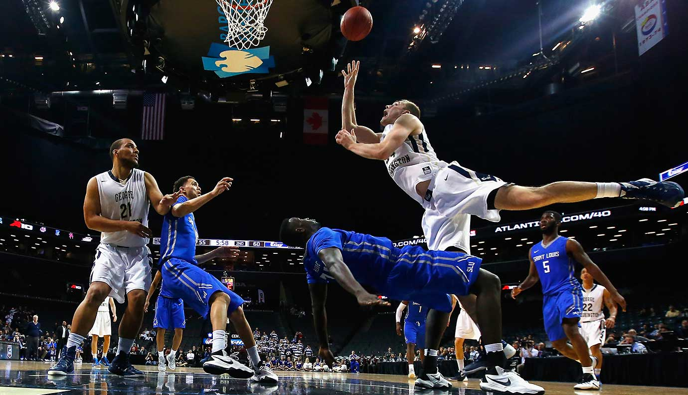 Tyler Cavanaugh of George Washington shoots against Reggie Agbeko of the Saint Louis Billikens.