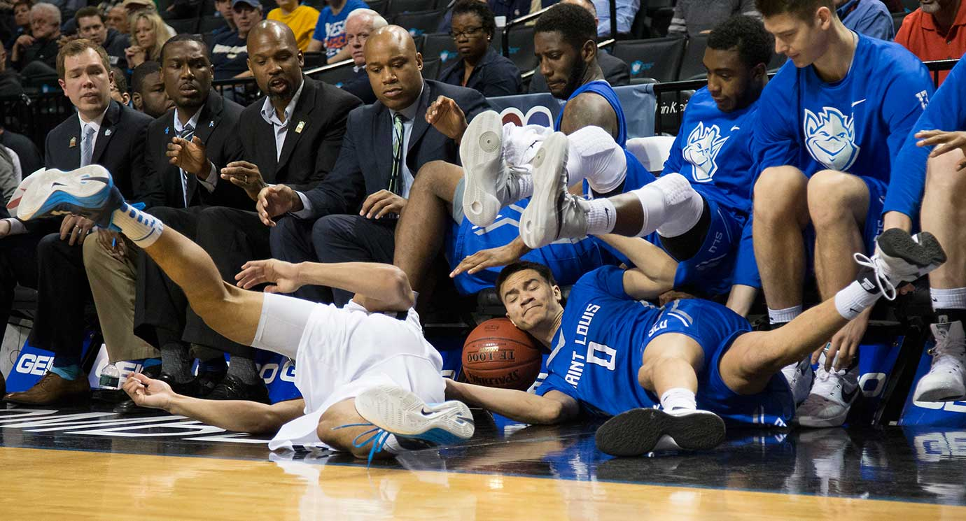 Marcus Bartley of Saint Louis and Joe McDonald of George Washington fall into the Billikens bench going after the ball.
