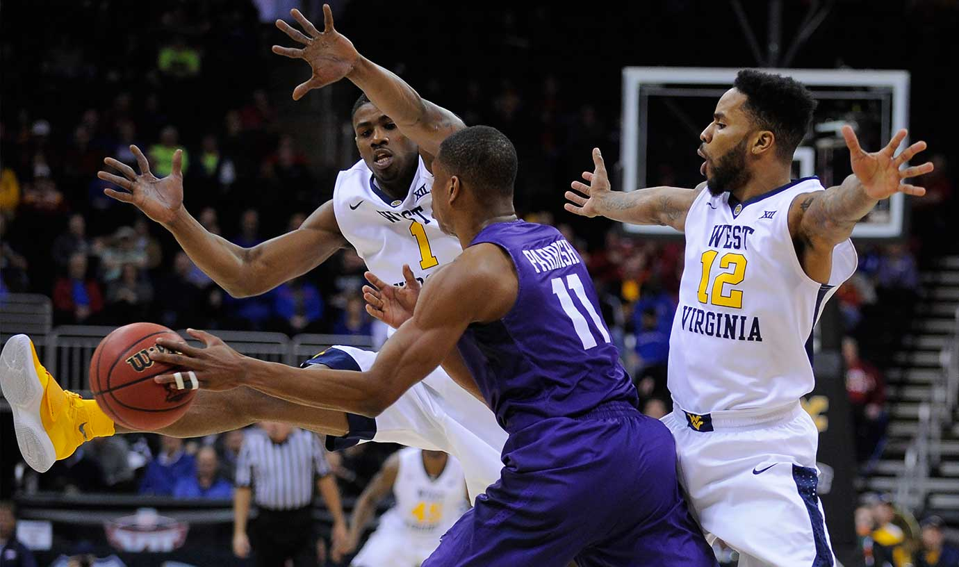 Brandon Parrish of TCU tries to pass against Jonathan Holton (1) and Tarik Phillip of West Virginia.