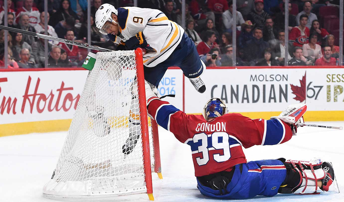 Evander Kane of the Buffalo Sabres collides with Mike Condon of the Montreal Canadiens.