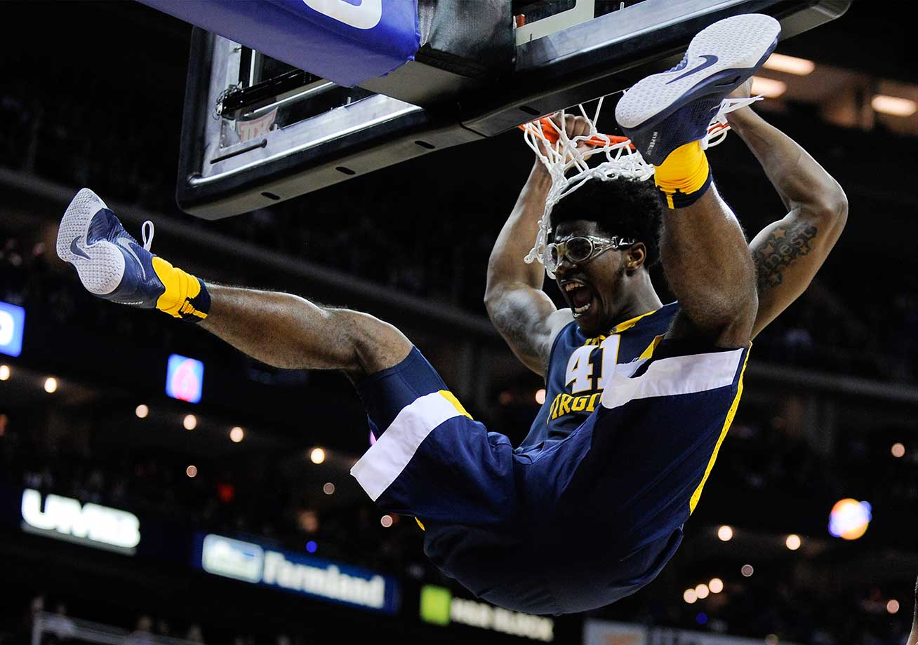 Devin Williams of West Virginia hangs on the rim after dunking against the Kansas Jayhawks.