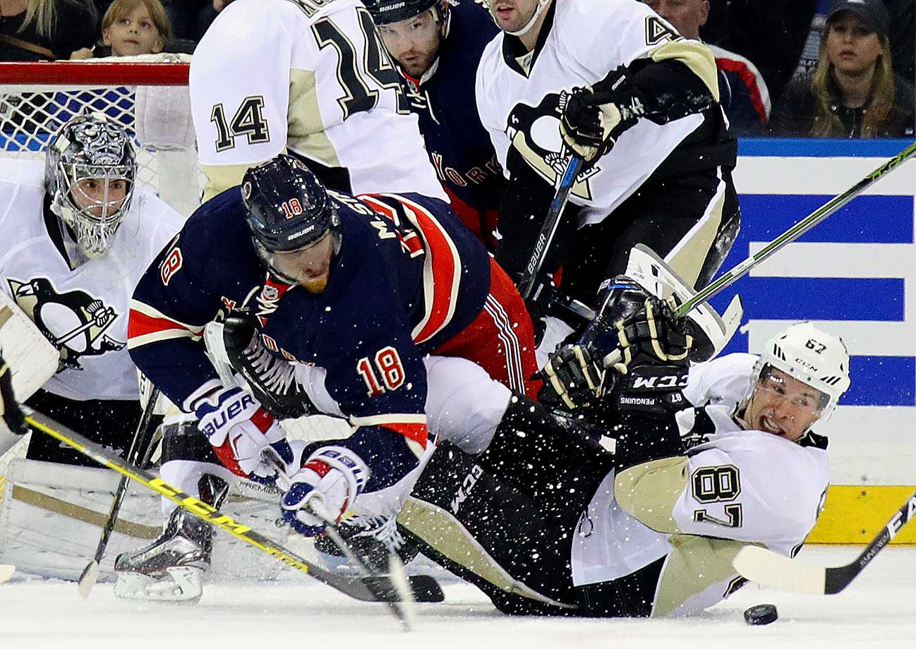 Marc Staal (18) of the New York Rangers trips over Sidney Crosby (87) of the Pittsburgh Penguins.