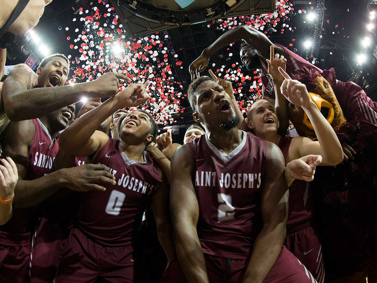 Lamarr Kimble (0), Aaron Brown (2) and the rest of the Saint Joseph's Hawks celebrate their win against VCU.