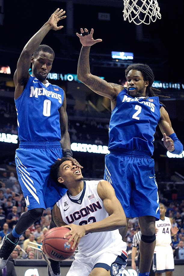 Connecticut's Shonn Miller is fouled by Memphis forward Trashon Burrell (0) while going up for a shot.