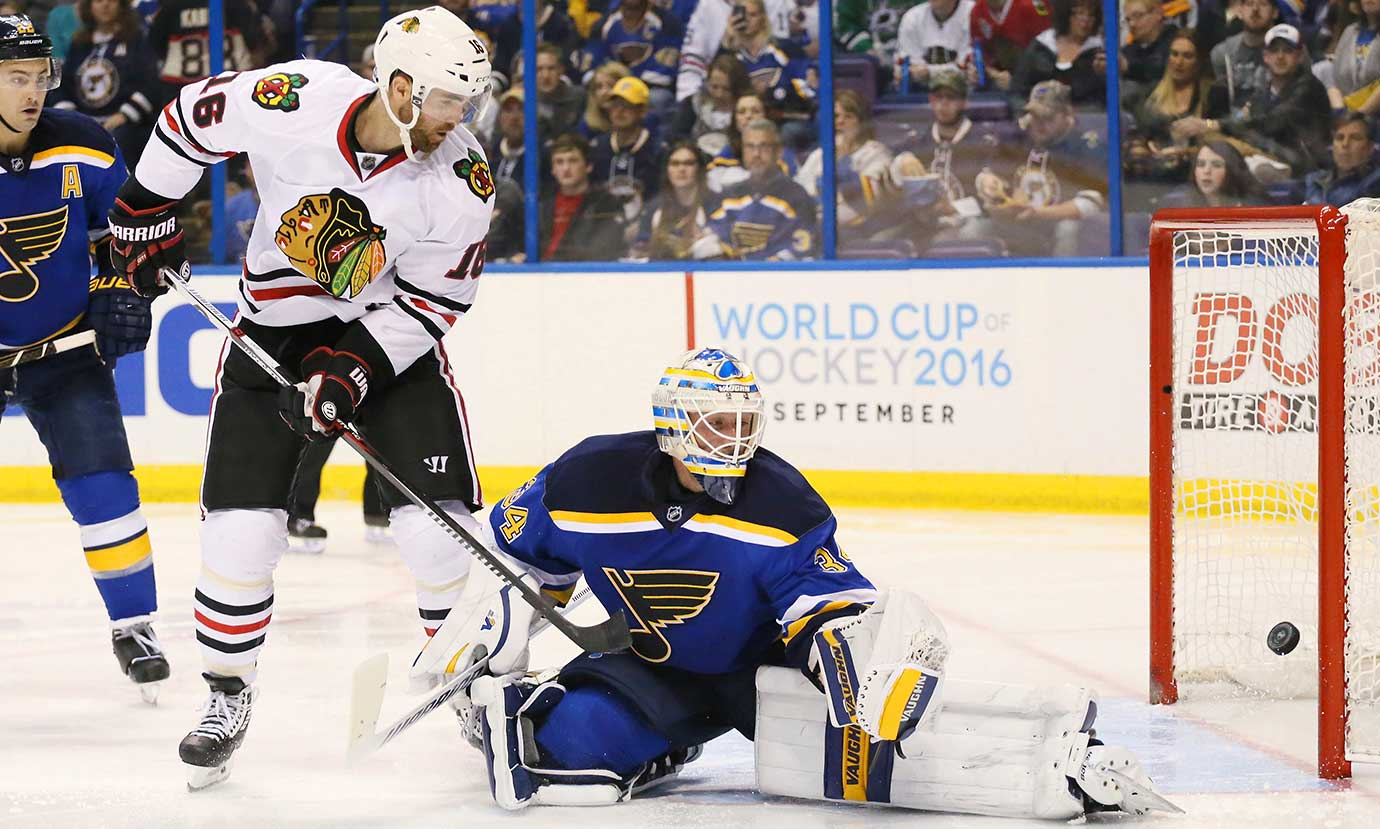 Andrew Ladd of the Chicago Blackhawks redirects a shot past St. Louis Blues goaltender Jake Allen.