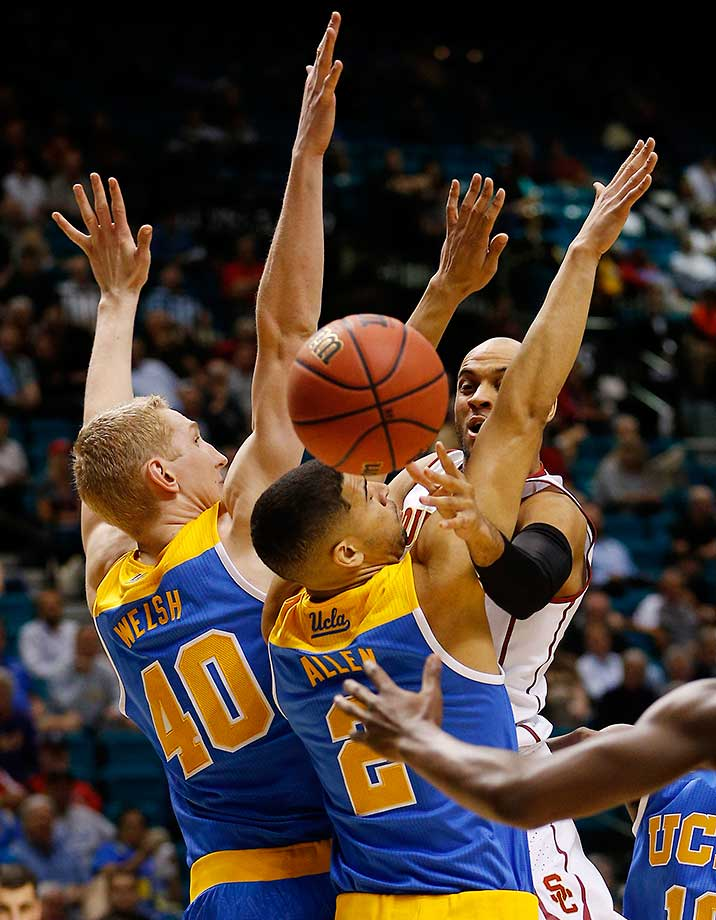 Southern California guard Julian Jacobs passes around UCLA guard Noah Allen and center Thomas Welsh.