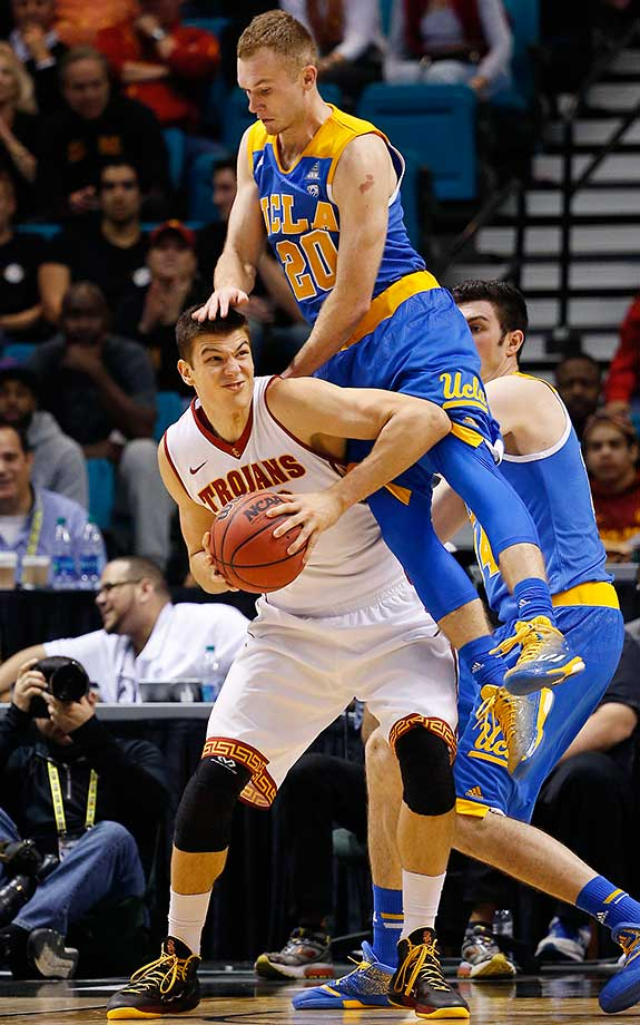 UCLA guard Bryce Alford falls onto Southern California forward Nikola Jovanovic in the Pac-12 tournament.