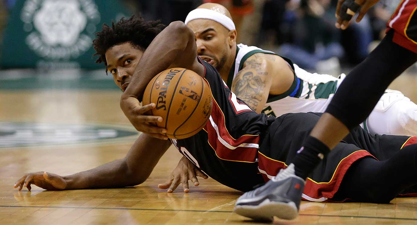 Miami's Justise Winslow, bottom, and Milwaukee's Jerryd Bayless scramble for a loose ball.