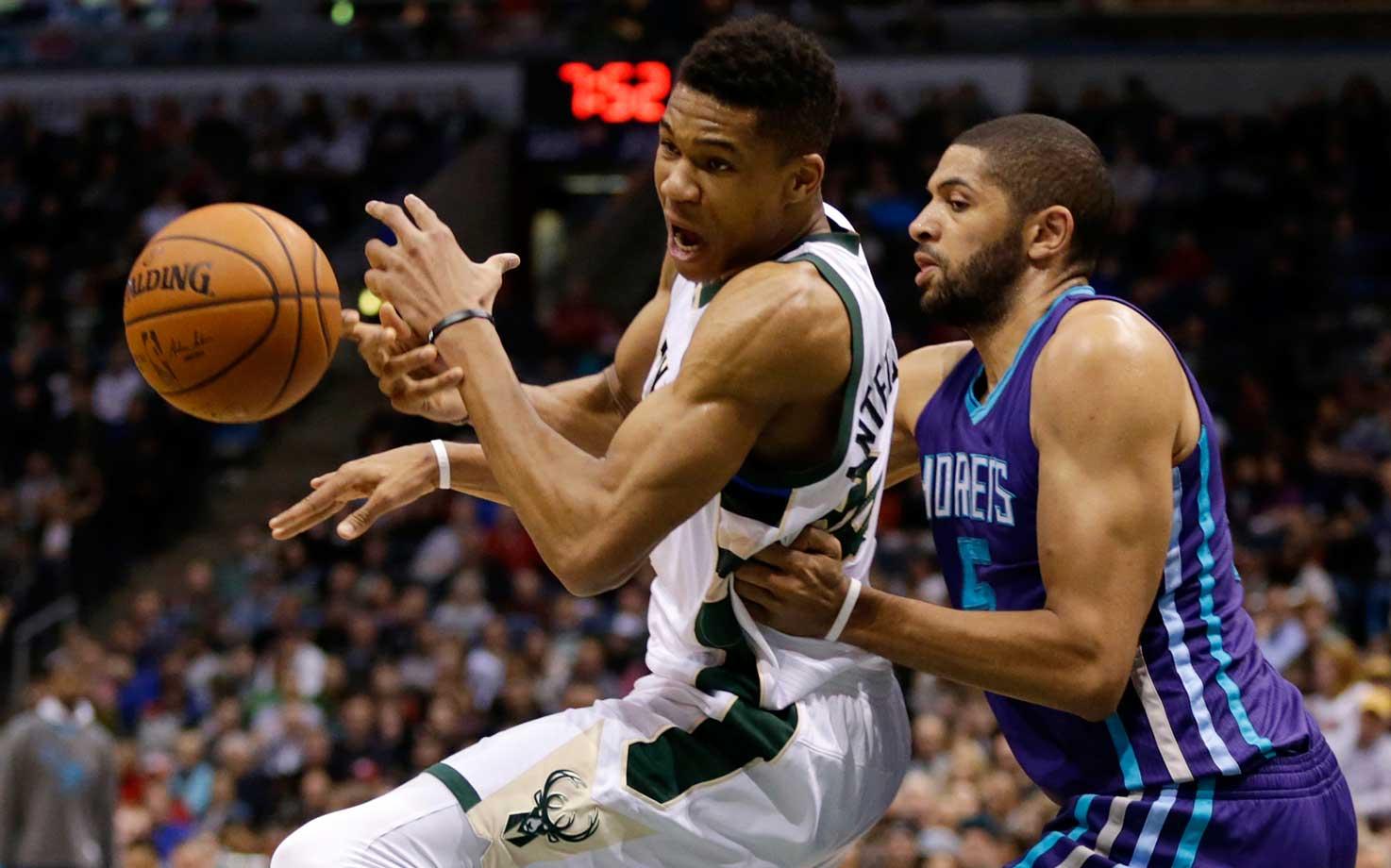 Nicolas Batum of the Charlotte Hornets picks the basketball from Giannis Antetokounmpo of the Milwaukee Bucks.