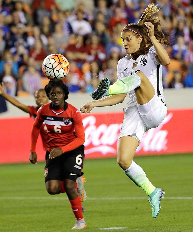 Alex Morgan shoots and scores a goal as Trinidad and Tobago's Khadidra Debesette (6) defends.