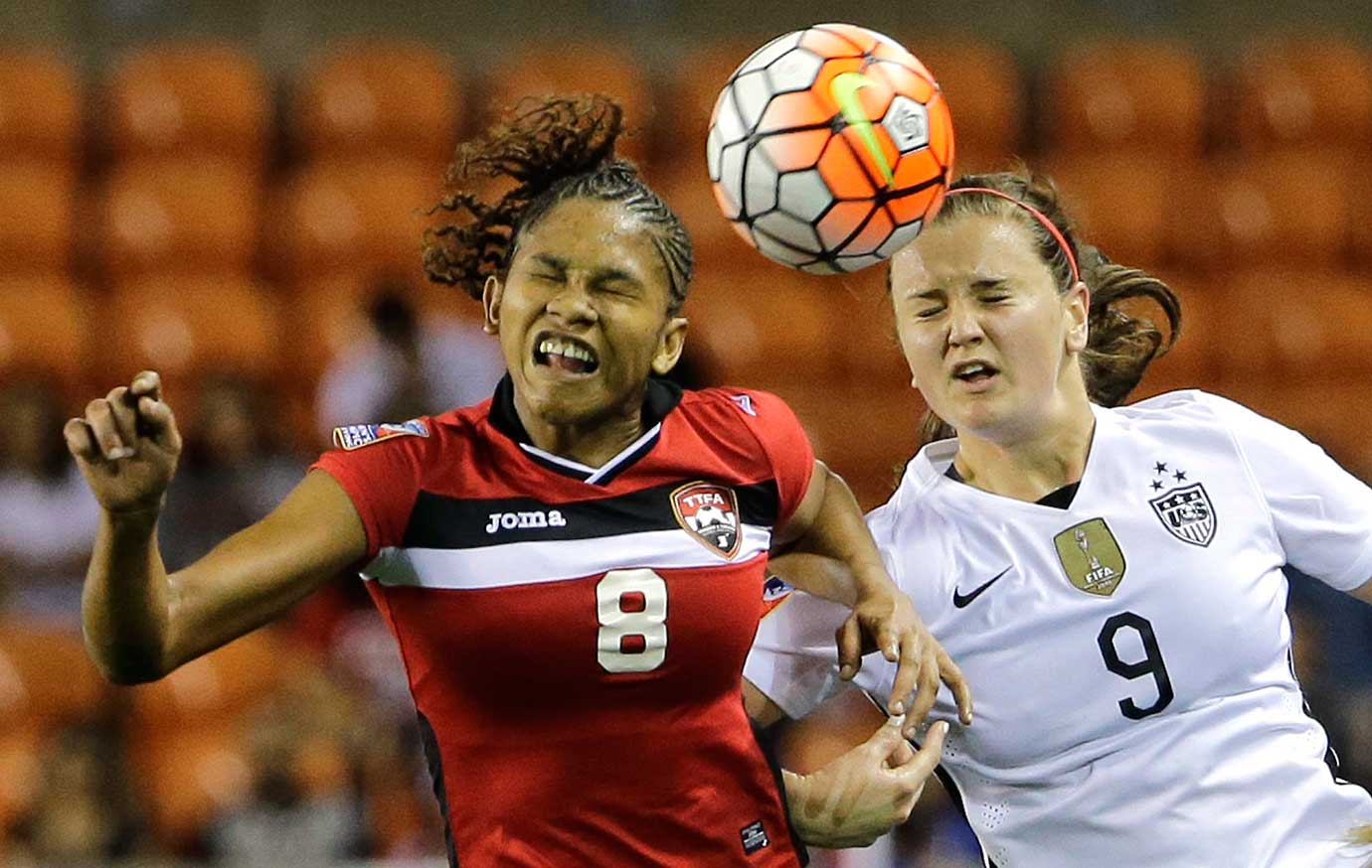 Trinidad and Tobago's Victoria Swift and Lindsey Horan of the U.S. go up for the ball.