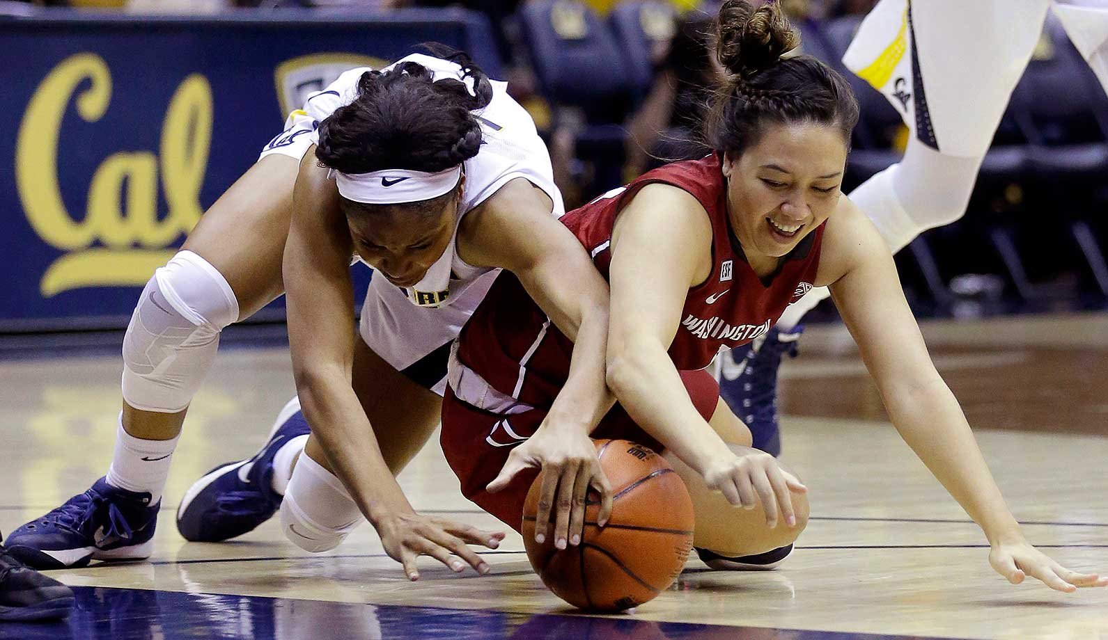 Washington State's Dawnyelle Awa, right, and California's Kristine Anigwe dive for the ball in Berkeley, Calif.