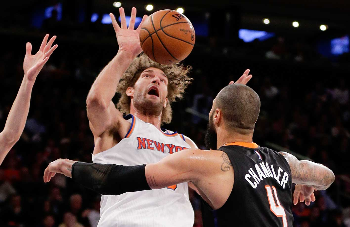New York Knicks center Robin Lopez reaches for a rebound against Phoenix center Tyson Chandler in New York. The Knicks won 102-84.