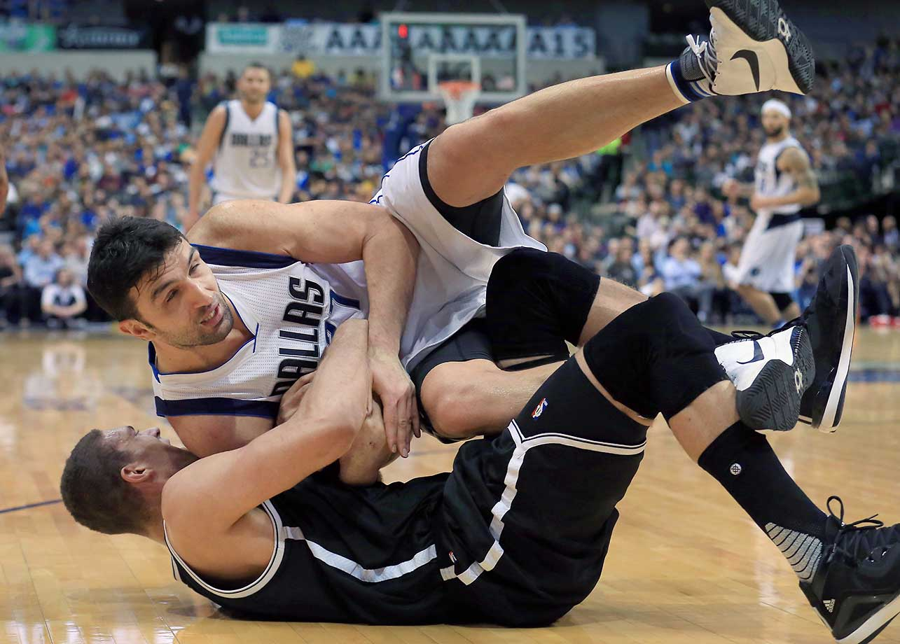 Zaza Pachulia of the Dallas Mavericks scrambles for the ball against Brook Lopez of the Brooklyn Nets at American Airlines Center on  in Dallas.