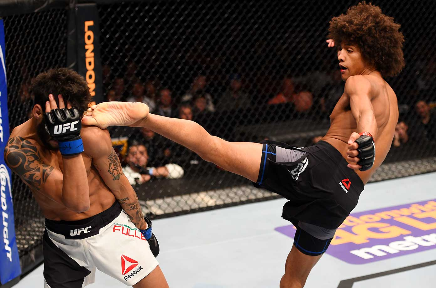 Alex Caceres kicks Masio Fullen in their featherweight bout during the UFC Fight Night event at the Prudential Center in Newark, New Jersey.