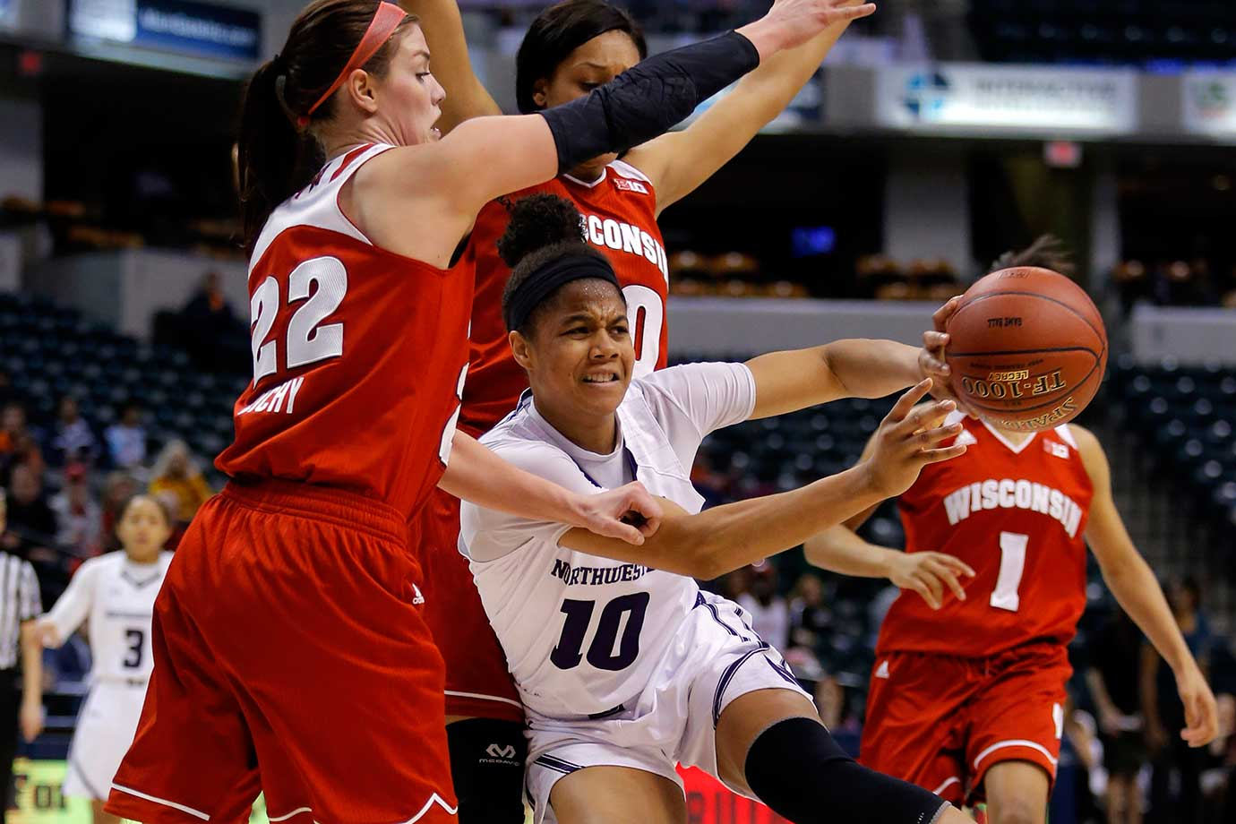 Northwestern's Nia Coffey makes a pass as she is stopped by Wisconsin's Tessa Cichy during the Big Ten Tournament.