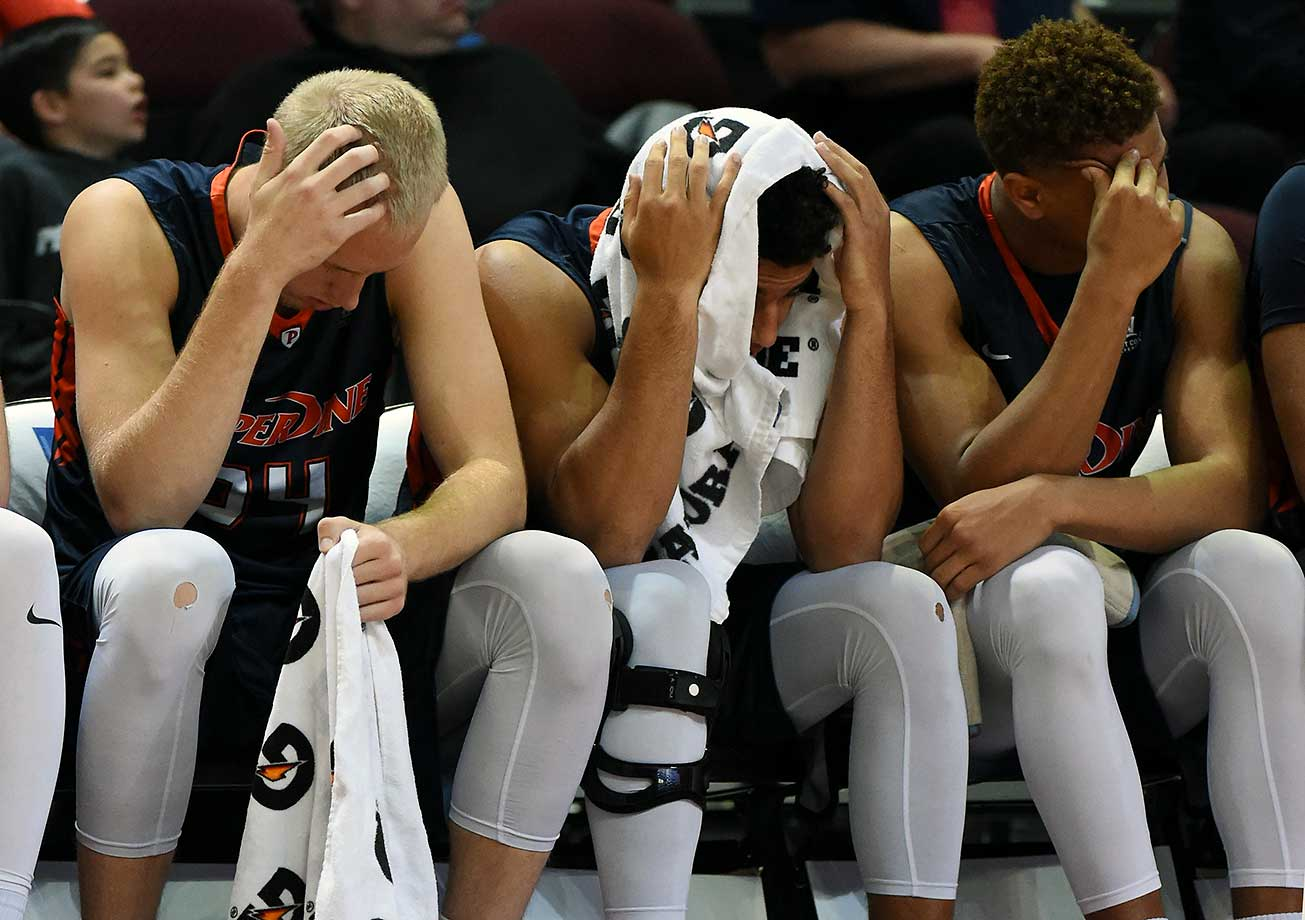 Jake Johnson, Jonathan Allen and Kameron Edwards of Pepperdine react late in their 81-66 loss to  Saint Mary's in a semifinal game of the West Coast Conference tournament.