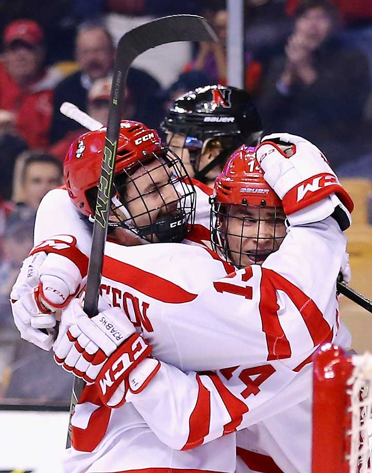 Robbie Baillargeon of the Boston University Terriers congratulates Bobo Carpenter (14) after he scored against the Northeastern Huskies at TD Garden in Boston,. The Eagles defeated the Crimson 3-2.