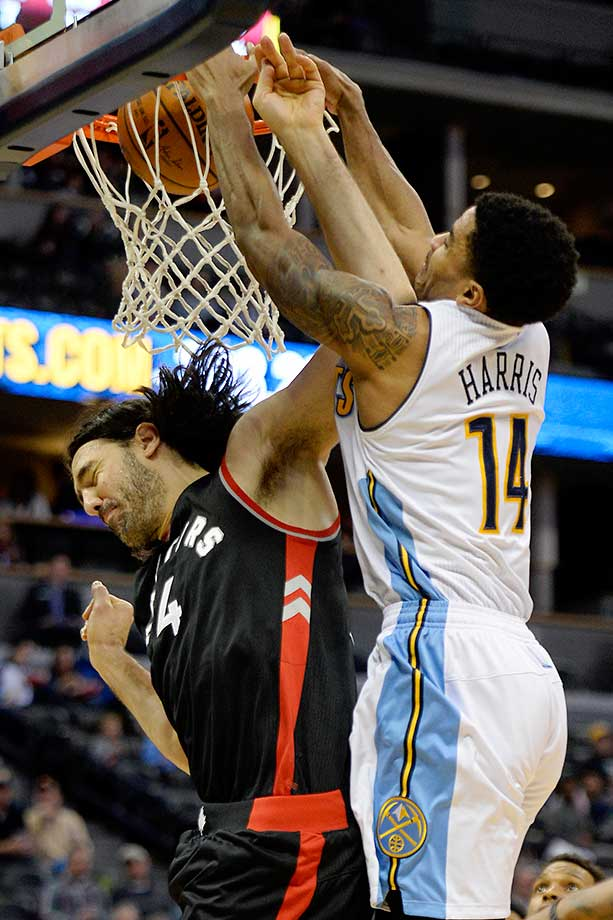 Gary Harris of the Denver Nuggets posterizes Luis Scola of the Toronto Raptorsat the Pepsi Center.