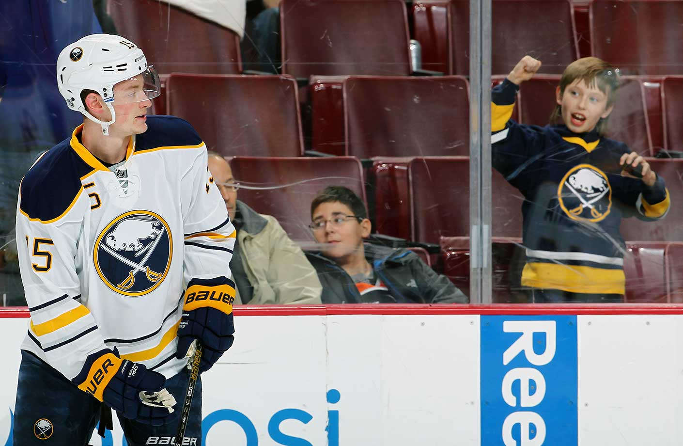 A fan reacts after receiving a puck from Jack Eichel of the Buffalo Sabres during warmups.