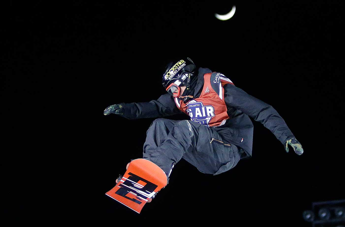 Snowboarder Mons Roysland of Norway  jumps with the moon behind during the Big Air at Fenway Park skiing and snowboarding event.